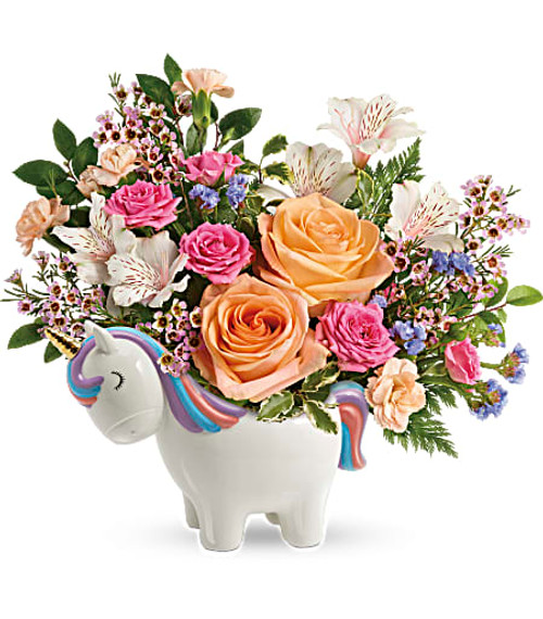 Make magic with this joyful gift of peach and pink roses, delicately arranged in this sweet ceramic unicorn keepsake that's hand-painted for an extra-special touch! Peach roses, pink spray roses, white alstroemeria, peach miniature carnations, blue sinuata statice, and pink waxflower are accented with huckleberry and pitta negra.