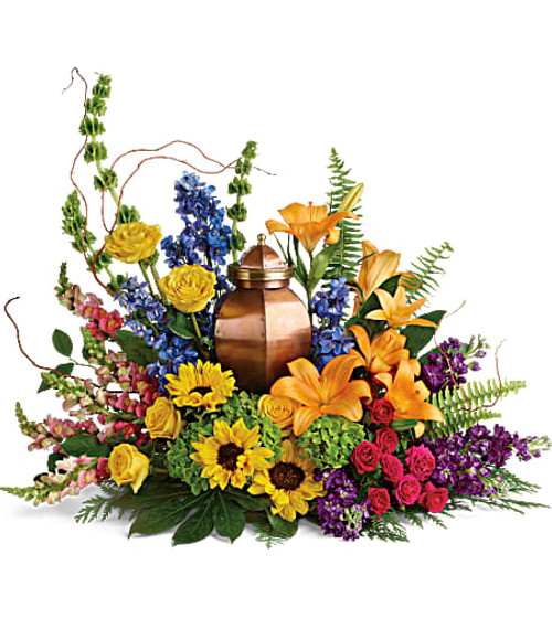 Like a radiant rainbow on a gray day, this colorful bouquet of hydrangea, roses, and sunflowers brings a bright light of hope to the cremation urn and celebration of life.