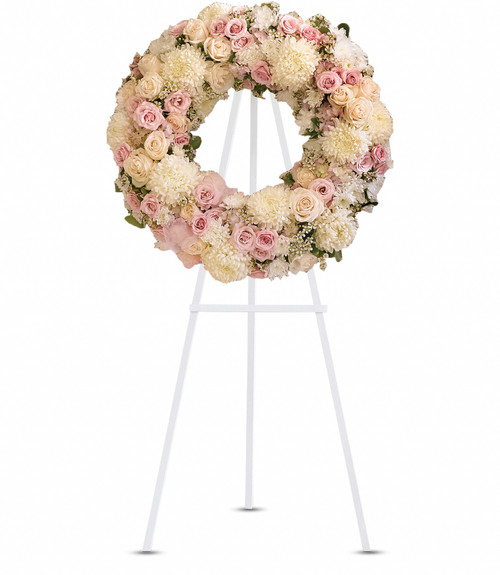 """Wreath with Gorgeous pink hydrangea, crème roses, light pink spray roses, white chrysanthemums, waxflower and more are adorned by pink organza ribbon in this eternal circle of peace. Approximately 24 1/2"""" W x 24 1/2"""" H"""