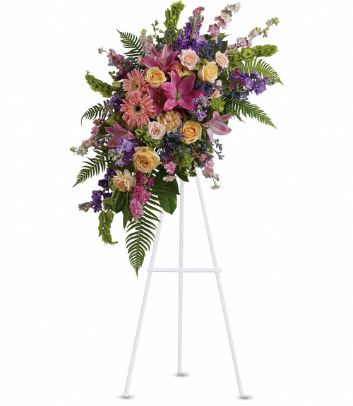 A standing spray in pinks, yellows, and lavenders