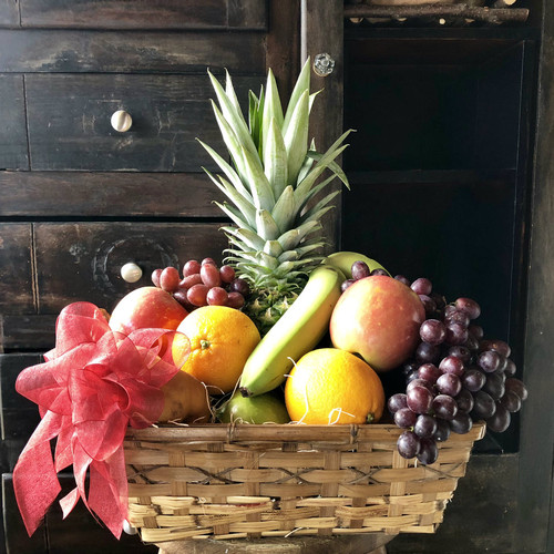 A wide assortment of the season's freshest fruit delicately placed in a wicker basket. Fruit may vary according to season and freshness.