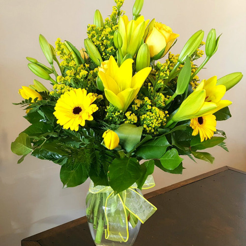 Our Bursting With Sunshine bouquet features yellow lilies, gerbera daisies, tulips, yellow roses and brings sunshine to any room.