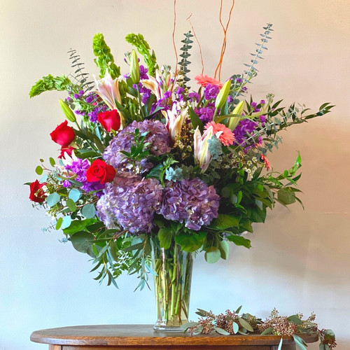 Garden Jewel is a glamorous design of red roses, purple hydrangea, stargazer lilies, pink gerbera daisies, purple stock, belles of Ireland, and eucalyptus.