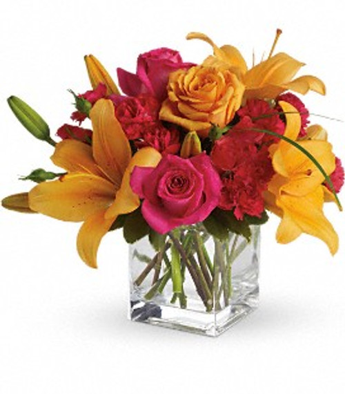 Bright orange and hot pink flowers in a clear glass cube