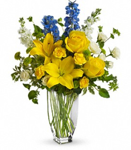 blue and yellow flowers in a clear vase