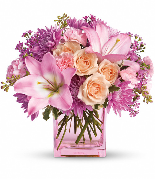 Pink and light peach flowers delivered in a pink glass cube.
