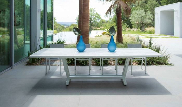 Side view of Amaka outdoor extension table with whitewashed concrete look HPL top and powder-coated white aluminium frame