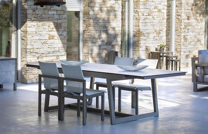 Les Jardins outdoor teak table with HPL top and matching Skaal dining chairs with Batyline Eden mesh