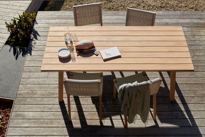 Classical looking Devon St Clair table in teak wood, displayed with Jackson side chairs in whitewash