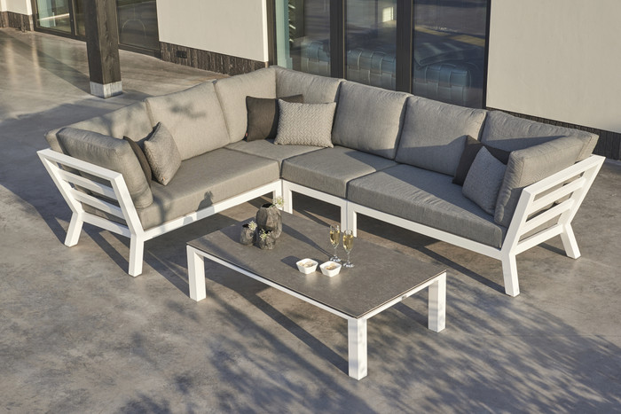 Timber outdoor corner lounge set with high arm in white powder-coated aluminium frame. Cushions in picture are similar in look to actual cushions supplied by Poynters. But our cushions have been upgraded to premium Sunbrella Fabric in Natte grey. There is also available, a single arm-less sofa to make the corner sofa longer, and arm chairs and 2.5 person sofa in the range. The coffee table pictured - CONCEPT -  is available. We also recommend the powder coated aluminium Leaf tables which are available in two colours and two sizes.