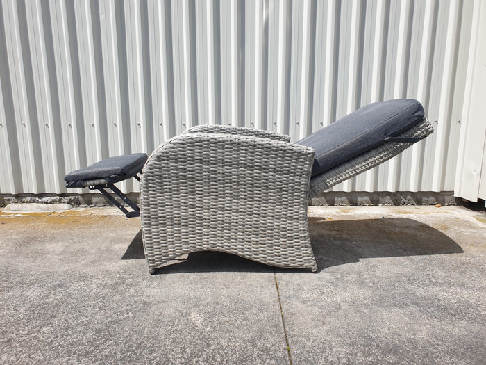 View of Divani outdoor fully adjustable outdoor wicker lounge chair, with leg rest and backrest fully extended.