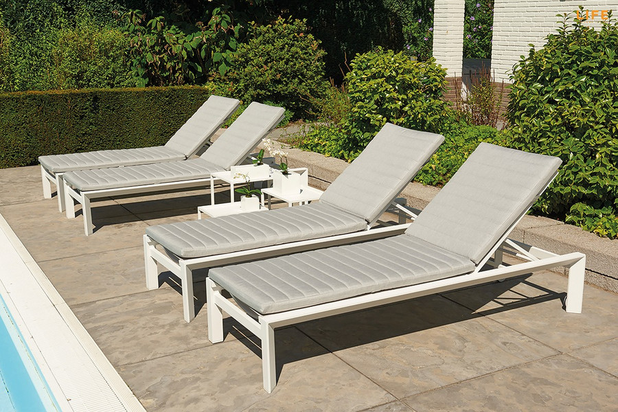 Another view of Delta white aluminium sun lounger with sunbrella cushion and headrest in Natte Grey. Great comfort and style