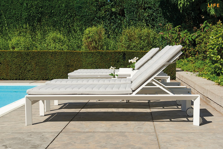 Side view of Delta white aluminium sun lounger with sunbrella cushion and headrest in Natte Grey. Great comfort and style