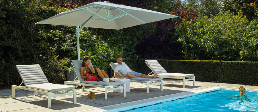 Delta white aluminium sun lounger with sunbrella cushion and headrest, with shade protection from our Roma cantilever side post umbrella. Great comfort and style.