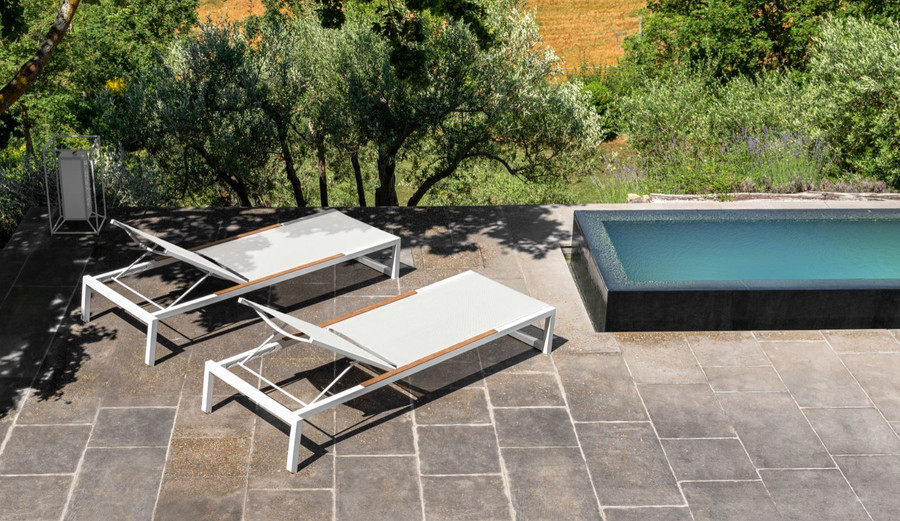 A pair of Alabama Alu Sun Loungers by Talenti in white frame with light grey textilene sling and teak accents