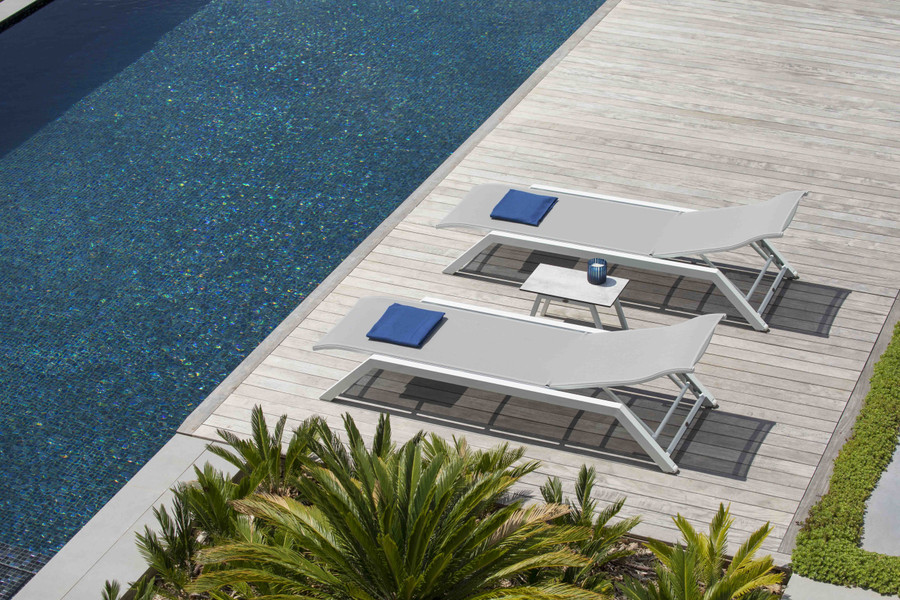 Ambient view of Amaka outdoor sun lounger - please note the white frame version is supplied with white batyline mesh, and grey frame version is supplied with dark grey mesh