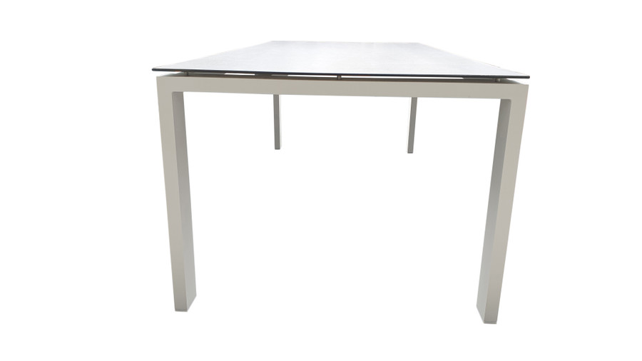 End view of Poly Ceramic top and aluminium frame outdoor dining table in 2 colour ways. Size 220x100 shown as reference to design only. Table shown is white frame with dark grey ceramic top.