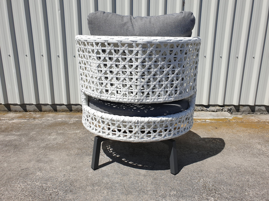 Rear view of Tiki outdoor swivel chair in white wicker with outdoor cushions.