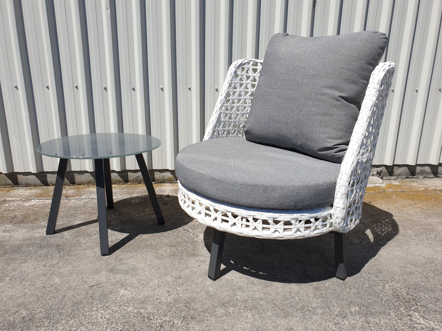 View of Tiki outdoor swivel chair in white wicker with matching Tiki side table - small