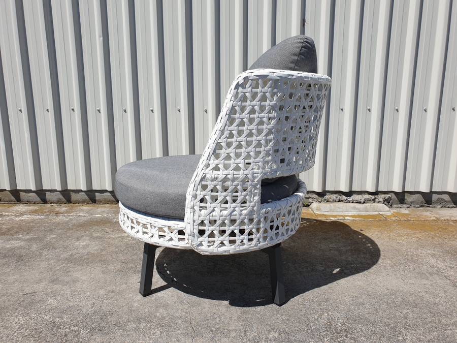 Side view of Tiki outdoor swivel chair in white wicker with outdoor cushions.