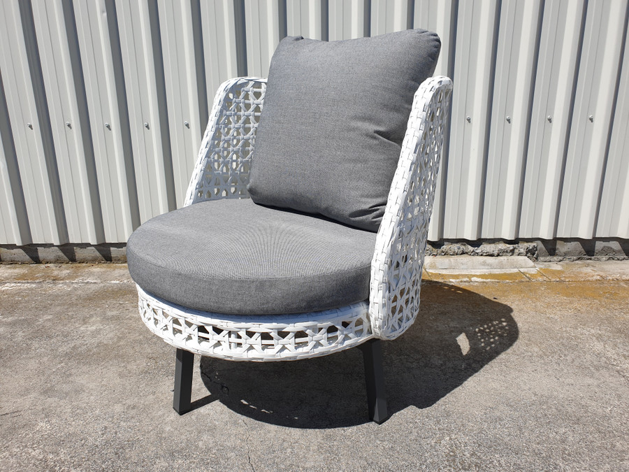 Angle view of Tiki outdoor swivel chair in white wicker with outdoor cushions.