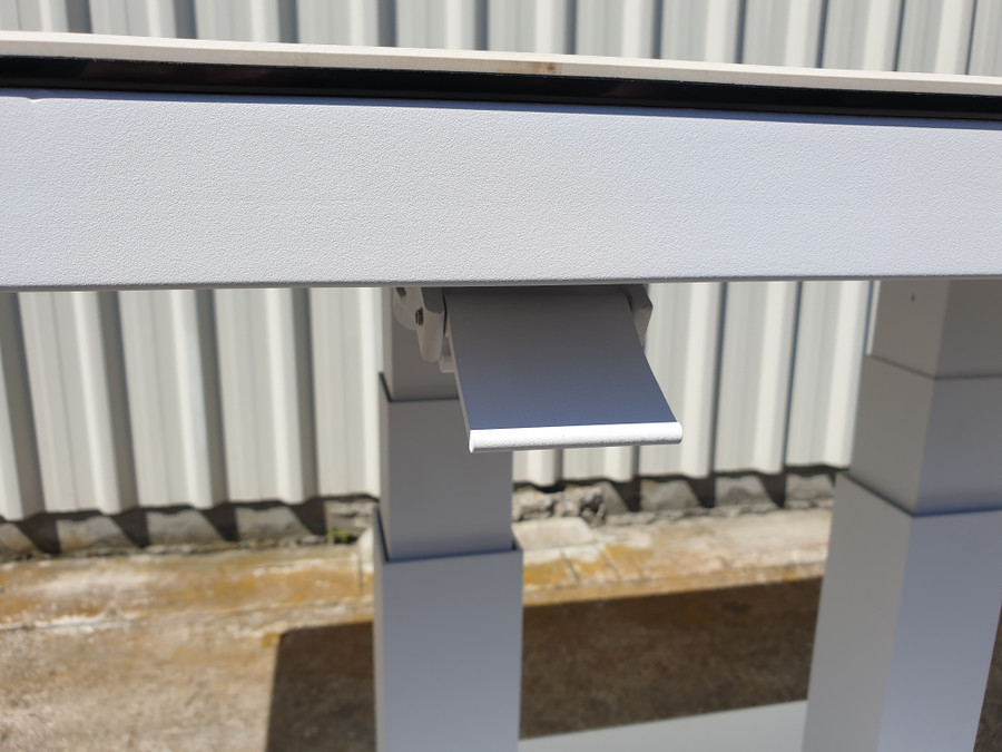 Tab lever on underside of table is used to adjust the height of the table