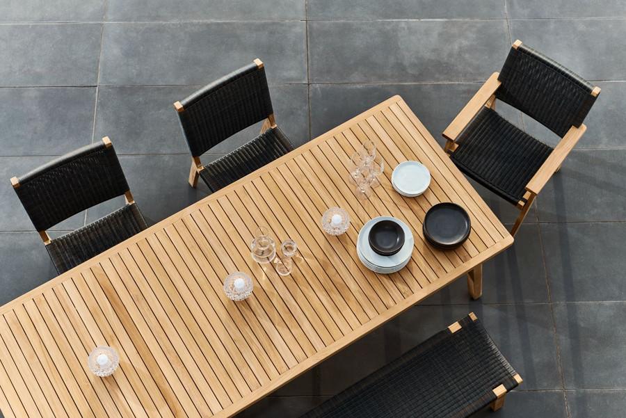 Devon Jackson teak and wicker outdoor dining chair shown with Devon Porter outdoor table