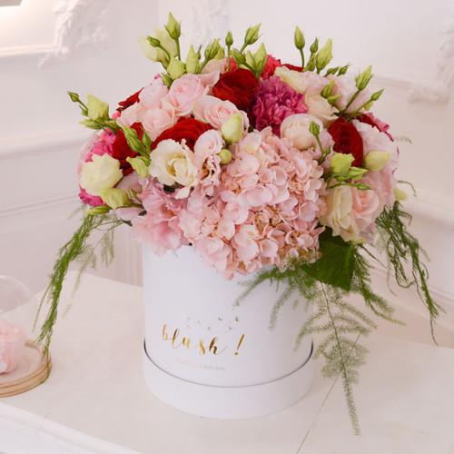 Boîte de fleurs composée de rose rouges et roses.