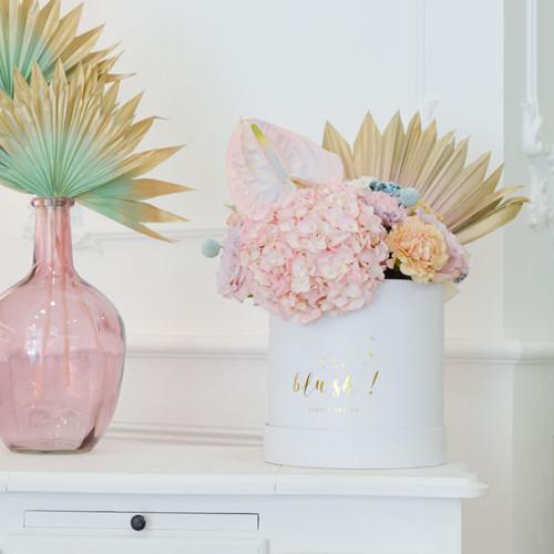 Boîte de fleurs fraîches composée de palmes séchées, d'hortensias roses et de roses roses.