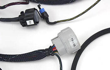 "OK, LSx friends! You are probably dreading going through that old wiring harness and pulling out the various pins and wires and making everything work together yourself.....or worse yet, sending your harness to ""Jake"" that works at your local insurance company, and does this kind of thing on the side! Well, look no further! We have exactly what you need to get on the road....no more surprises from what you attempted to do, no more lost time pulling pins from the Blue ECM or Green ECM and having to tie them all together or removing a ton of wires (which is what is required).  wiringharnessb.jpg  All that being said, this is the quickest and easiest way to be running and on the road with your LS project. This will work with your crate motor, your junkyard motor, or the transplant from a running candidate in your stable.  The harness is ready to go! All of the unnecessary wires are removed! Only wires essential to your LSx swap running the way it was meant to be.  They're made with XLP heat and fire resistant wire and new OEM connectors. They include the OBDII diagnostic/tuning port and a weatherproof fuse relay panel with diagram. The woven nylon covering is much better looking, easier to route, and will not wear on other components like factory convoluted tubing.  connectors.jpg   Also included with the kit is an OE engine control module that has been re-flashed to remove all of the unnecessary elements like vehicle anti-theft system (VATS) and secondary o2 sensors.  It is then tuned for a stock to mild camshaft with shift points to work for most builds. If you are running a strange combo or a large camshaft email us for a different pre-program or your final tune can be made on a local tuners dyno. Everything is tested on a running engine before it leaves the factory. Just plug it in and start enjoying your new LS swap! NOTHING COULD BE EASIER!"