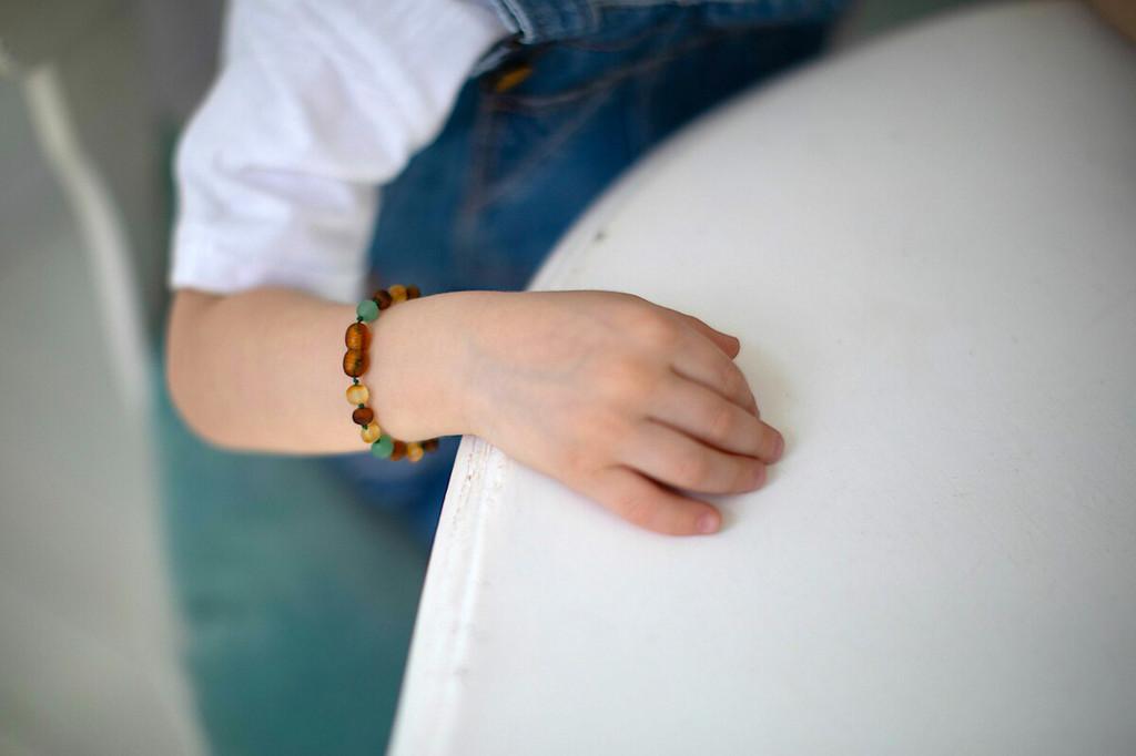 Matte green agate amber teething bracelet on hand
