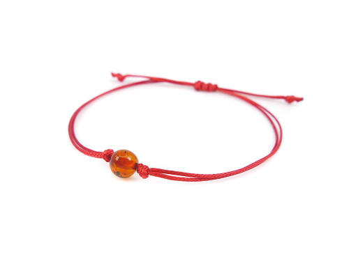 Red string bracelet with cognac amber