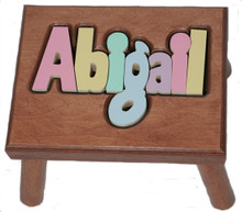 cherry puzzle name stool, shown with pastel letters