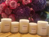 4 oz and 8 oz frosted jars filled with all natural coconut oil wax or soy wax sitting on a marble counter top in front of a purple and mauve rose flower arrangement.