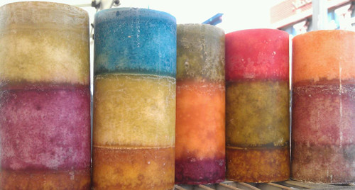 """grouping of 3""""x7.25"""" round pillar candles with three colors each. Earth tones."""