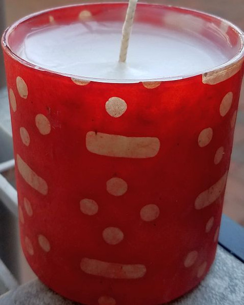 Red background with white dots and dashes. Uniquely scented candles in decoupaged containers.