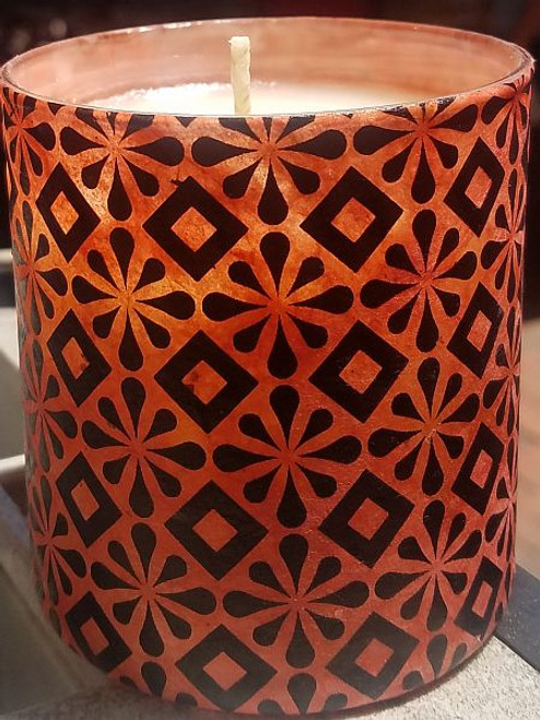 Orange paper with black diamonds and stars. Uniquely scented candles in decoupaged containers.These containers are covered with paper or fabric.