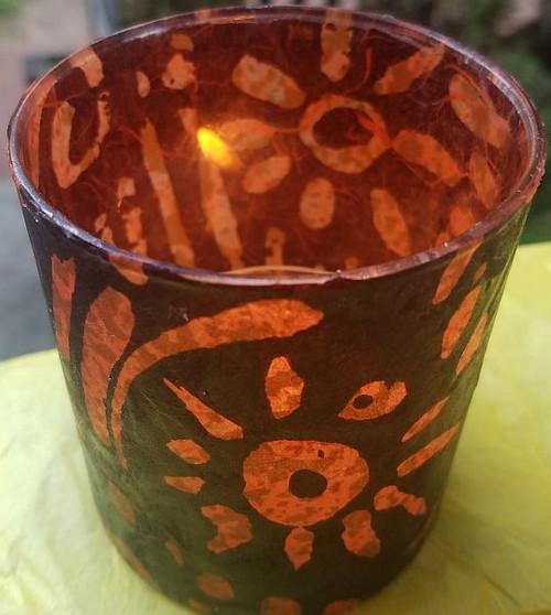 This paper has a batik orange tribal design on a black translusent paper