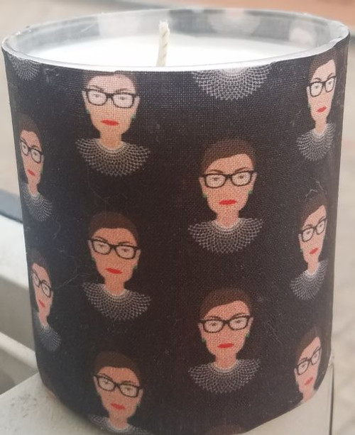 This candle has tiny Ruth Bader Ginsberg busts with dissent collar that repeat. the background is black.