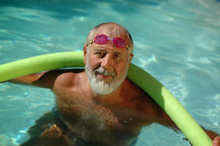 elderly man swimming with noodle and goggles
