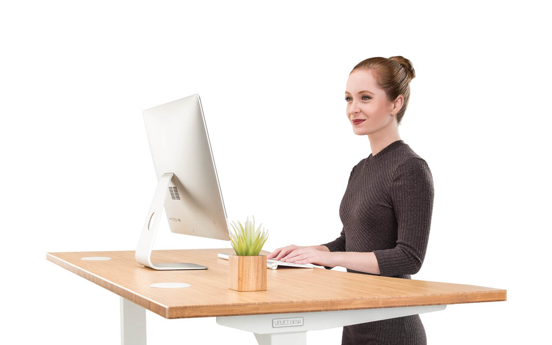 A woman stands at her UPLIFT Desk bamboo with her ear piece in helping customers