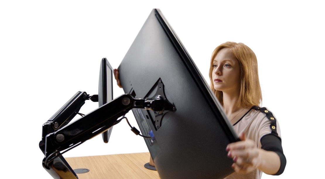 woman adjusts a monitor arm on an UPLIFT Standing Desk