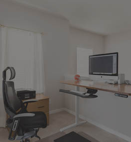 home office with standing desk and tiered keyboard tray
