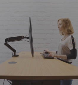 woman tasks comfortably at a standing height adjustable desk by UPLIFT Desk