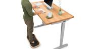 """60"""" x 30"""" natural ash Solid Wood Desk on a gray UPLIFT V2 Standing Desk Frame"""