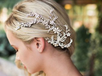 Rhodium plated hair comb with enamel flowers and rhinestone accents.