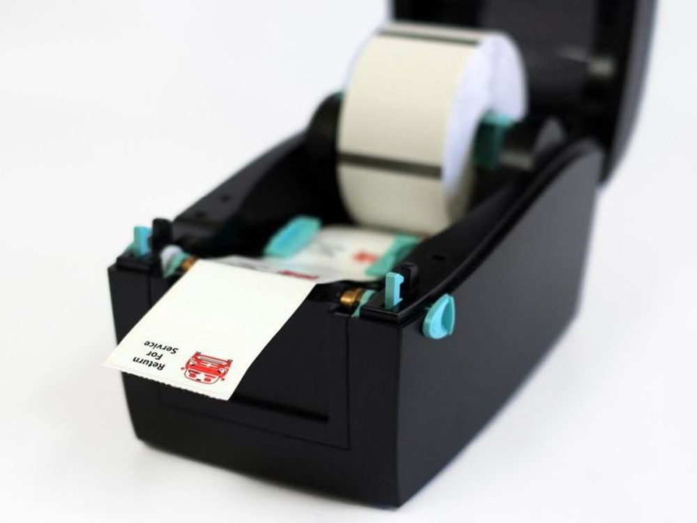 How a roll of oil change stickers is loaded into the printer system