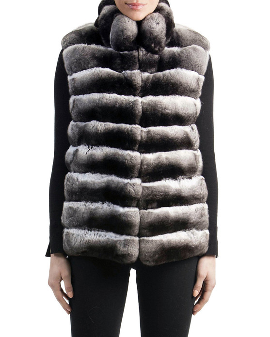 chinchilla vest   with stand up collar worn over black tight blouse with sleeve slits and black tight pants