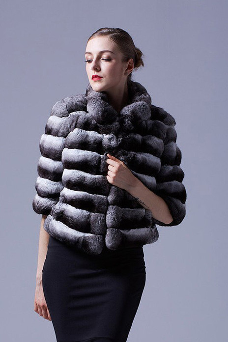 Short chinchilla jacket with elbow cut sleeves on model with french twist and black tight dress
