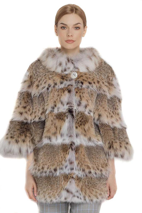 lynx fur coat stitched with skins acrooss elbow length sleeves and white lynx collar on blond model with checked cotton pants and elegant haircut